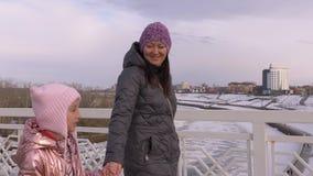 Figlia sorridente che si tiene per mano e che parla con la madre Passeggiate da parte a parte archivi video