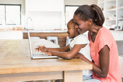 Figlia sveglia che per mezzo del computer portatile allo scrittorio con la madre Fotografia Stock