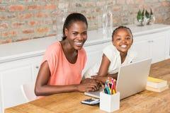 Figlia sveglia che per mezzo del computer portatile allo scrittorio con la madre Fotografia Stock Libera da Diritti