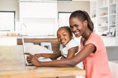 Figlia sveglia che per mezzo del computer portatile allo scrittorio con la madre Fotografie Stock