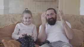 Figlia sveglia del ritratto piccola con suo padre divertente che gioca i video giochi sulla TV con le grandi emozioni in salone a archivi video