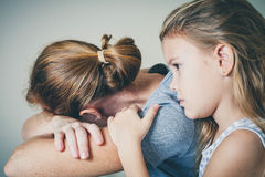 Figlia triste che abbraccia sua madre Immagine Stock