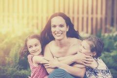 Figlie che abbracciano la loro madre - retro Immagine Stock Libera da Diritti