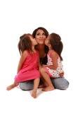 Figlie sveglie che baciano la loro mamma Fotografia Stock