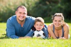 Figlio allegro e genitori che si trovano nel campo di football americano immagini stock