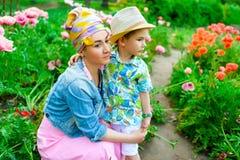 Figlio amoroso che abbraccia sua madre alla moda in parco Fotografie Stock Libere da Diritti