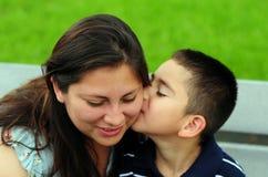 Figlio che bacia mamma sulla guancica fotografie stock