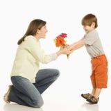 Figlio che dà i fiori della madre. Fotografie Stock Libere da Diritti
