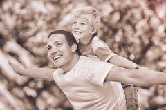 Figlio che gioca con suo padre nel parco durante l'estate fotografie stock libere da diritti