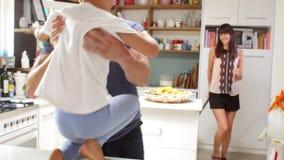 Figlio che gioca nella madre di saluto della cucina che ritorna dal viaggio video d archivio