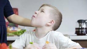 Figlio che mangia panino sulla cucina, mamma che prepara panino per il figlio, famiglia felice video d archivio