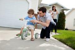 Figlio d'istruzione del padre per guidare triciclo Fotografie Stock