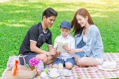 Figlio d'istruzione della famiglia teenager asiatica mentre picnic nel parco immagine stock