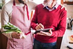 Figlio dei pantaloni a vita bassa con suo padre senior con la compressa nella cucina Immagine Stock Libera da Diritti