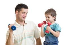 Figlio del bambino e del padre che fa esercizio con la testa di legno Fotografia Stock
