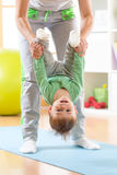 Figlio del bambino e della donna che fa gli esercizi di yoga alla stuoia Immagine Stock