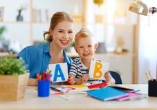 Figlio del bambino e della madre che fa scrittura di compito e che legge a casa fotografie stock