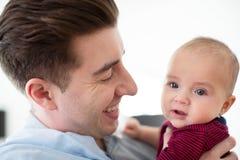 Figlio di amore di Cuddling Cute Baby del padre a casa immagine stock