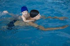 Figlio di insegnamento del padre da nuotare nello stagno dello swimmimg Divertendosi con il papà fotografia stock libera da diritti