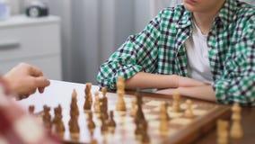 Figlio di insegnamento del padre per giocare scacchi, sviluppo di pensiero logico, hobby della famiglia stock footage