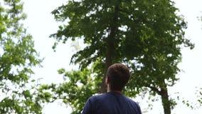 Figlio di lancio del padre in aria, movimento lento Padre e figlio divertendosi in un parco verde, padre che getta giovane ragazz video d archivio
