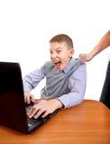 Figlio di trascinamento del genitore dal computer portatile Immagini Stock