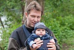 Figlio di trasporto del giovane padre in imbracatura in sosta immagini stock libere da diritti