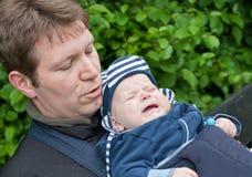 Figlio di trasporto del giovane padre in imbracatura in sosta fotografie stock libere da diritti