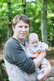 Figlio di trasporto del giovane padre nella foresta di estate immagini stock libere da diritti