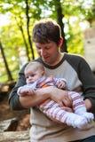 Figlio di trasporto del giovane padre nella foresta di estate fotografie stock libere da diritti