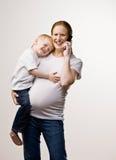 Figlio di trasporto della madre mentre comunicando sul telefono Immagini Stock