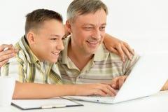 Figlio e padre che per mezzo del computer portatile Fotografie Stock