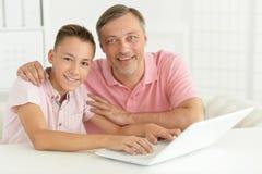 Figlio e padre che per mezzo del computer portatile Immagine Stock