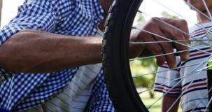 Figlio e padre che riparano la loro bicicletta in parco video d archivio