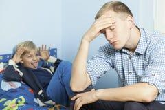 Figlio maleducato ed suo padre stanco Immagini Stock