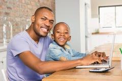 Figlio sveglio che per mezzo del computer portatile allo scrittorio con il padre Immagini Stock Libere da Diritti