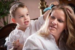 Figlio sveglio che spazzola i capelli della sua mamma immagini stock