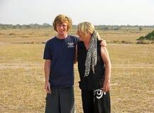 Figlio teenager e più vecchia risata matura della madre felici sul safari Africa Immagini Stock