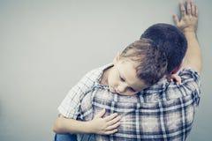 Figlio triste che abbraccia il suo papà Immagini Stock