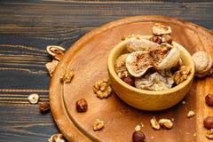 Figos e porcas secados no fundo de madeira Fotos de Stock Royalty Free