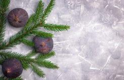 Figos frescos em um fundo concreto com uma árvore de Natal verde, vista lateral Close-up foto de stock