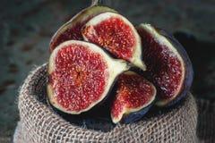 Figos maduros vermelhos doces em um grupo das mentiras no suporte Fotos de Stock