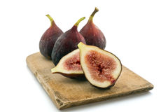 Figs. Three whole figs and one sliced one isolated on white Royalty Free Stock Images