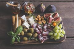Figs,camembert cheese,prosciutto ,olives, grapes on dark serving board over rustic wooden background Stock Images