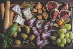 figs,camembert cheese,prosciutto ,olives, grapes on dark serving board over rustic wooden background. view from above Stock Photography