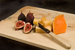 Figs and Cheese. Figs and two kinds of cheese on cutting board Royalty Free Stock Photography