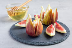 Figs, cheese, pistachio and honey dessert on slate plate, horizontal Royalty Free Stock Photography