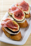 Figs with cheese and prosciutto. Sliced purple figs with cheese and prosciutto on toast Stock Image