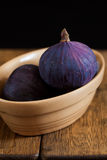 Figs in a china bowl. Fresh figs in a small brown china bowl, on a wooden surface, with a black background stock photo