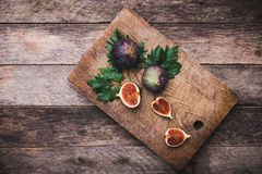 Figs on chopping board and wooden table Stock Photography